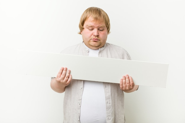Кавказский сумасшедший блондин толстяк с плакатом Premium Фотографии