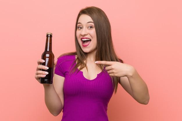 Молодая кавказская женщина держа бутылку пива Premium Фотографии