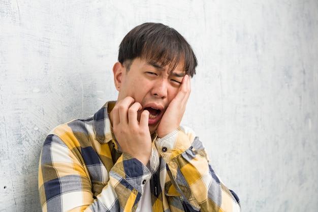 若い中国人男性の顔のクローズアップ、絶望的で悲しい Premium写真