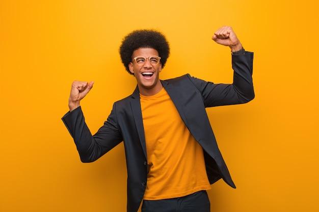 Молодой бизнес афроамериканец человек над оранжевой стеной, который не сдается Premium Фотографии