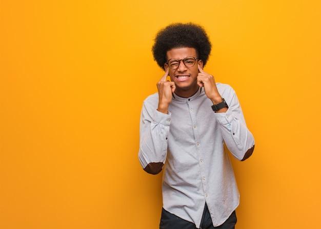手で耳を覆うオレンジ色の壁の上の若いアフリカ系アメリカ人 Premium写真