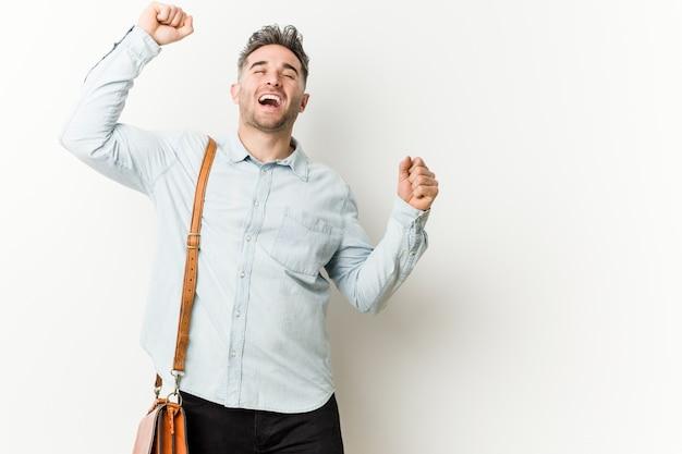 特別な日を祝う若いハンサムなビジネスマンがジャンプし、エネルギーで腕を上げます。 Premium写真