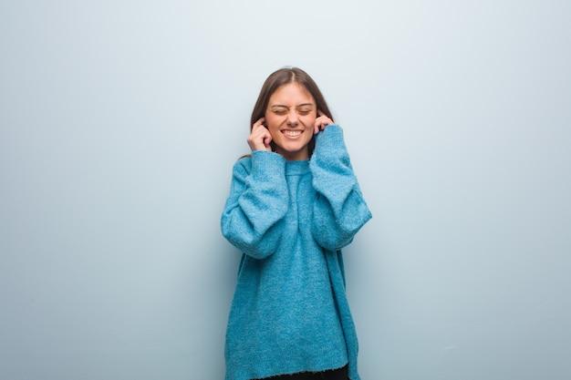 手で耳を覆う青いセーターを着ている若いきれいな女性 Premium写真