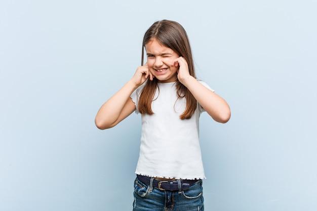 かわいい女の子が彼の手で耳を覆っています。 Premium写真