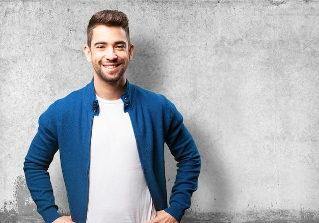 灰色の背景に腰に手で笑顔マン 無料写真