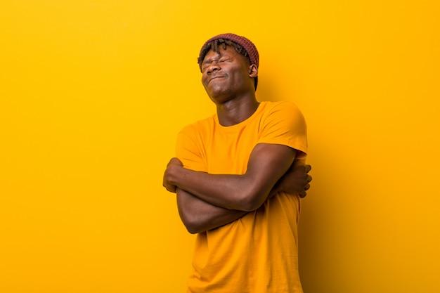 Молодой чернокожий мужчина в растах над желтым обнимает себя, улыбаясь беззаботным и счастливым. Premium Фотографии