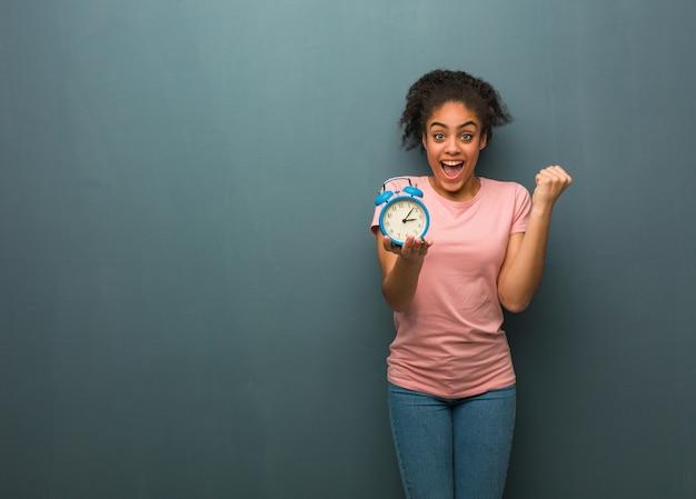 Молодая негритянка удивлена и шокирована. она держит будильник. Premium Фотографии