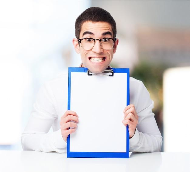 Улыбаясь человек показывает контрольный стол Бесплатные Фотографии