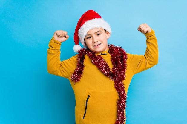 サンタ帽子を身に着けているクリスマスの日を祝っている小さな男の子分離された腕、女性の力の象徴と強さのジェスチャーを示す Premium写真