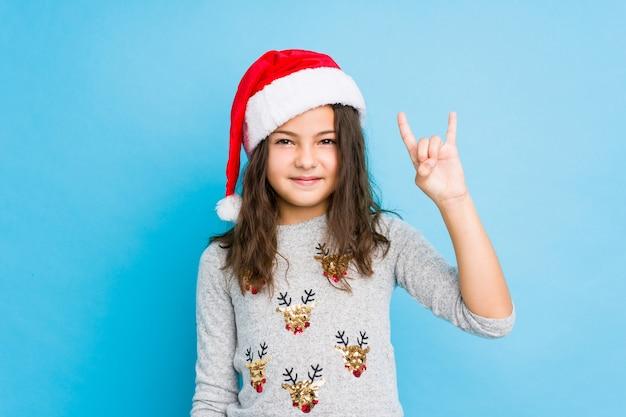 Маленькая девочка празднуя рождество показывая жест рожков как концепция революции. Premium Фотографии