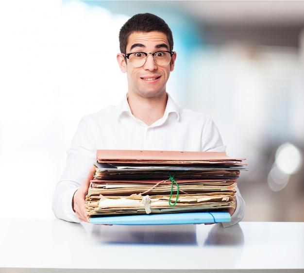 Человек, перевозящих кучу папок в офисе Бесплатные Фотографии
