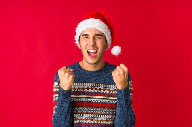 クリスマスの日に手で耳を覆う若い男。 Premium写真