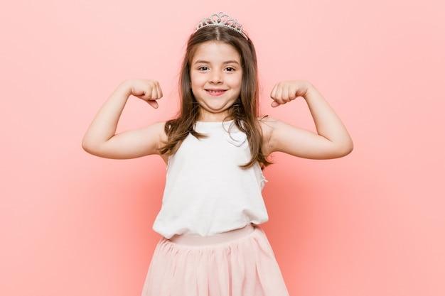 腕で強さのジェスチャーを示すプリンセスの外観を着ている少女 Premium写真