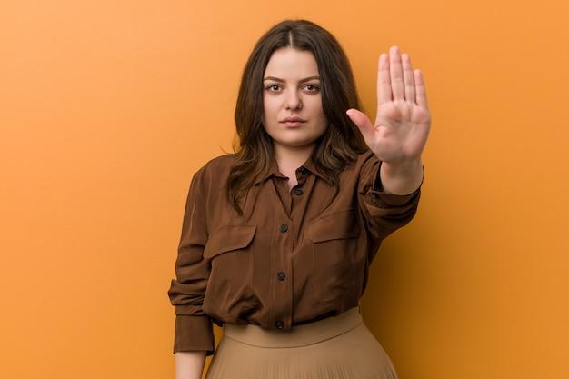 Молодая соблазнительная русская женщина, стоя с протянутой рукой, показывая знак остановки Premium Фотографии