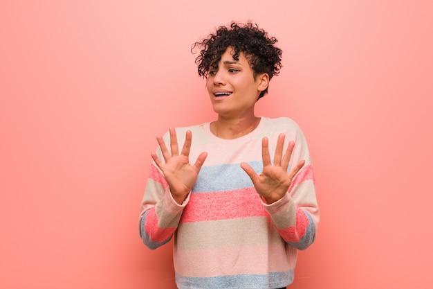 Молодая смешанная афро-американская женщина подростка отвергая кто-то показывая жест отвращения Premium Фотографии