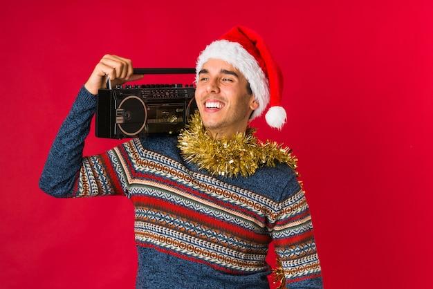クリスマスの日に贈り物を持って若い男 Premium写真