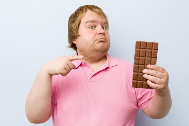 Кавказский сумасшедший белокурый толстый мужчина держит шоколадную таблетку Premium Фотографии