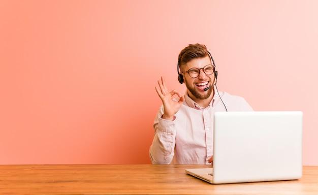 Молодой человек, работающий в колл-центр подмигивает глаз и держит хорошо жест рукой. Premium Фотографии