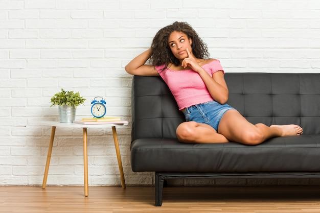 疑わしいと懐疑的な表情で横に見てソファに座っている若いアフリカ系アメリカ人女性。 Premium写真