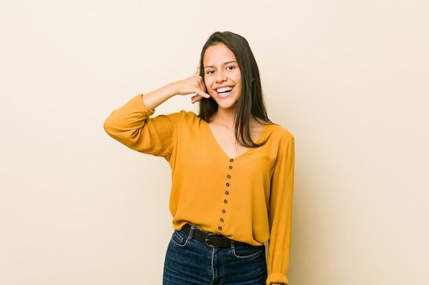 指で携帯電話呼び出しジェスチャーを示すベージュの壁に若いヒスパニック系女性。 Premium写真