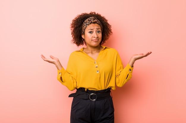 ジェスチャーを疑って肩をすくめてピンクの壁に若いアフリカ系アメリカ人女性。 Premium写真
