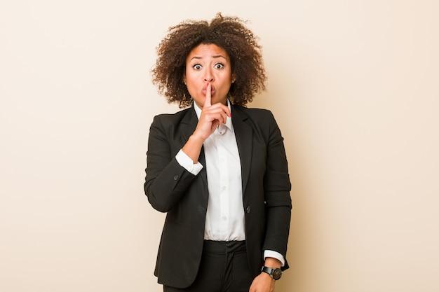 若いビジネスアフリカ系アメリカ人女性の秘密を守るか、沈黙を求めます。 Premium写真