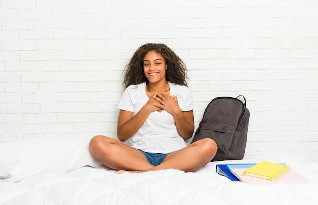 Молодой афроамериканец студент женщина на кровати имеет дружелюбное выражение, прижимая ладонь к груди. концепция любви Premium Фотографии