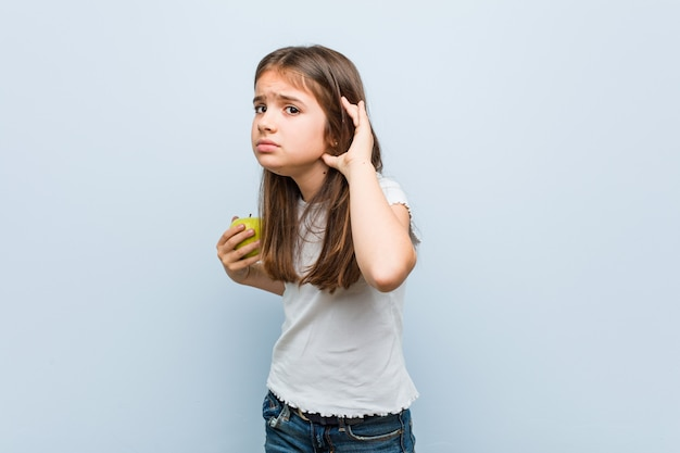 ゴシップを聴こうとして青リンゴを保持している白人少女。 Premium写真