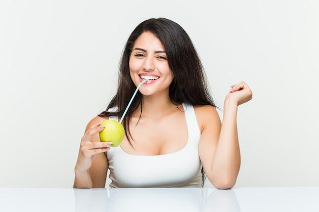 ストローでリンゴジュースを飲む若いヒスパニック系女性 Premium写真