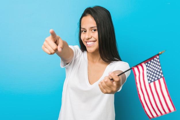アメリカ合衆国を保持している若いヒスパニック系女性は正面を向いて陽気な笑顔をフラグします。 Premium写真