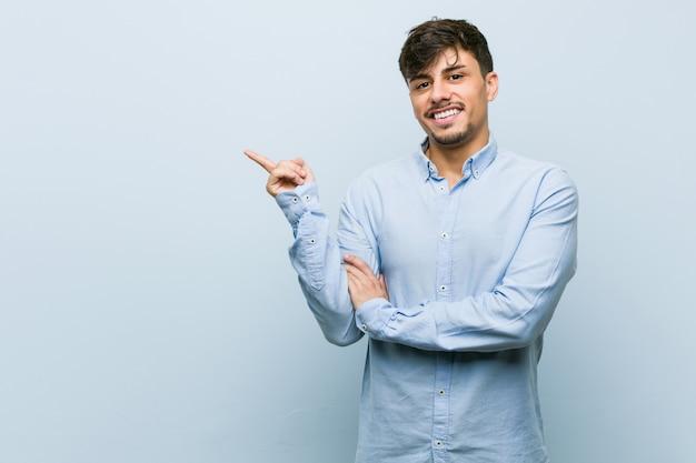 人差し指で元気に指している笑顔若いヒスパニックビジネス男。 Premium写真