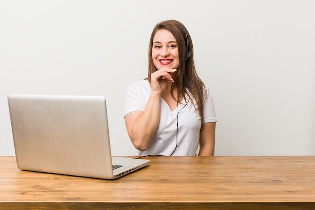 Молодой телемаркетер женщина улыбается счастливым и уверенным, касаясь подбородка рукой. Premium Фотографии
