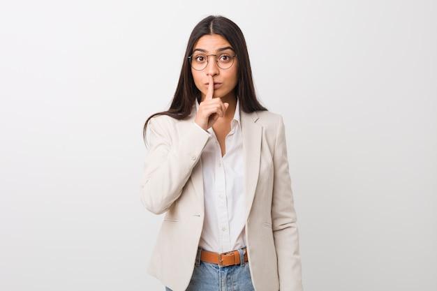 秘密を守るか沈黙を求める白い壁に対して隔離される若いビジネスアラブ女性。 Premium写真