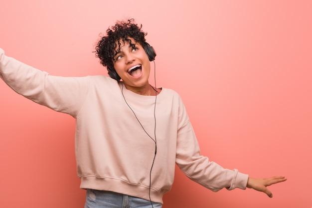 あざダンスとヘッドフォンで音楽を聴くと若いアフリカ系アメリカ人女性 Premium写真