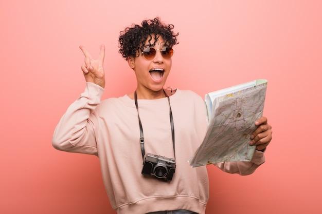 勝利のサインを示し、広く笑顔の地図を保持している若いアフリカ系アメリカ人女性。 Premium写真