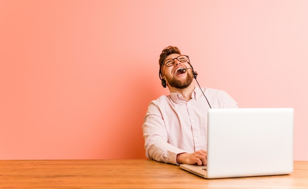 Молодой человек, работающий в колл-центр расслабленной и счастливый смех, шея растягивается, показывая зубы. Premium Фотографии