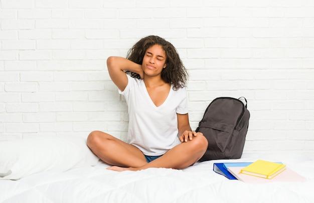 座りがちな生活のため首の痛みに苦しんでいるベッドの上の若いアフリカ系アメリカ人学生女性。 Premium写真