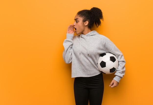 Молодой фитнес негритянка шепот сплетни подтекст. проведение футбольного мяча. Premium Фотографии
