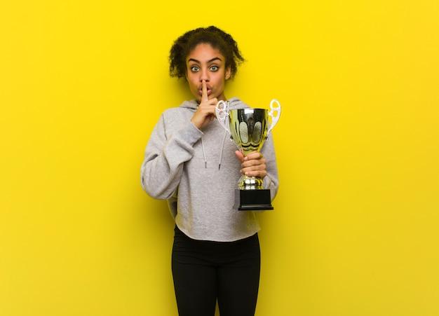 若いフィットネス黒人女性の秘密を守るか沈黙を求めています。トロフィーを保持しています。 Premium写真