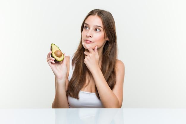 疑わしいと懐疑的な表情で横に見ているアボカドを保持している若い白人女性。 Premium写真
