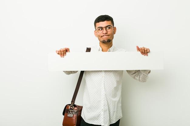 プラカードを保持している若いヒスパニックの実業家 Premium写真