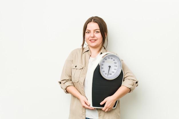 Молодая соблазнительная женщина, держащая весы, счастливая, улыбающаяся и веселая. Premium Фотографии