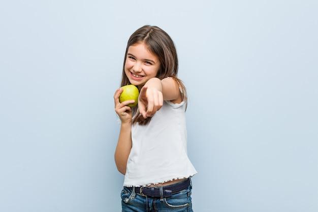 正面を指している青リンゴ陽気な笑顔を保持している白人少女。 Premium写真