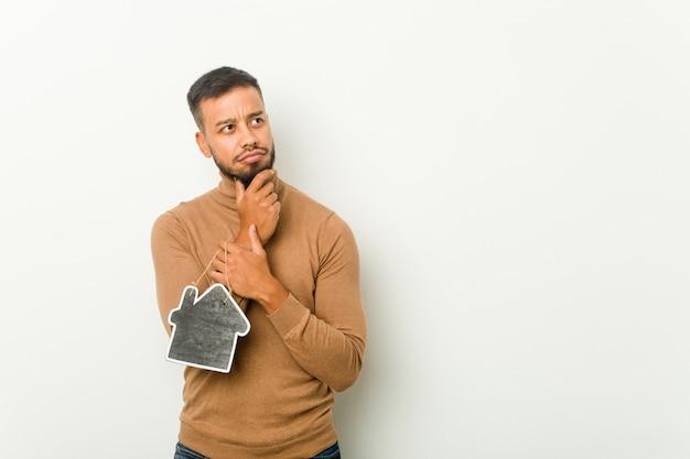 疑わしいと懐疑的な表情で横向きのホームアイコンを保持している若い南アジアの男。 Premium写真