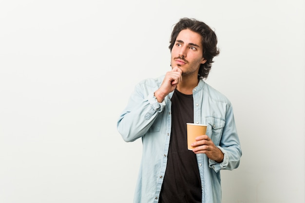 疑わしいと懐疑的な表情で横向きにコーヒーを飲む若いクールな男。 Premium写真