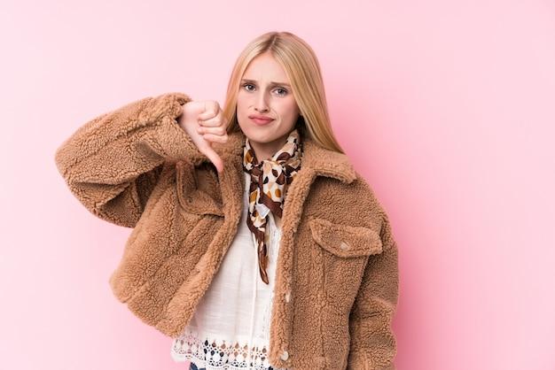 嫌いなジェスチャー、親指ダウンを示すピンクの壁にコートを着ている若いブロンドの女性。不一致の概念。 Premium写真