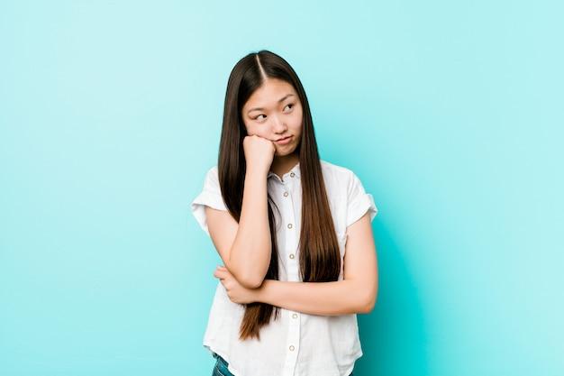 Молодая милая китайская женщина которая чувствует уныла и задумчива, смотрящ космос экземпляра. Premium Фотографии