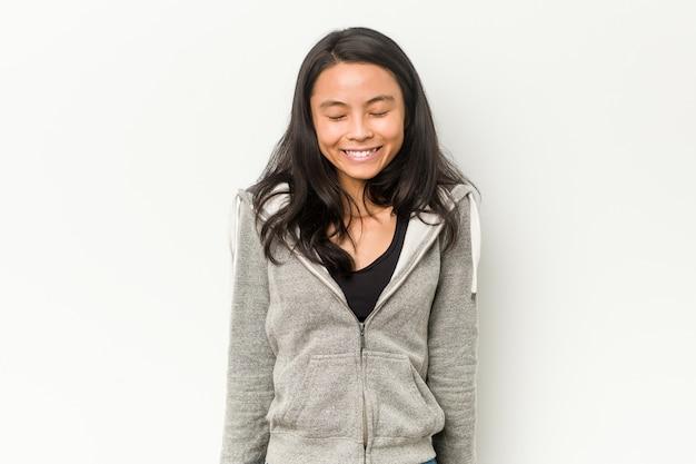若いフィットネス中国人女性は笑って目を閉じ、リラックスして幸せを感じています。 Premium写真