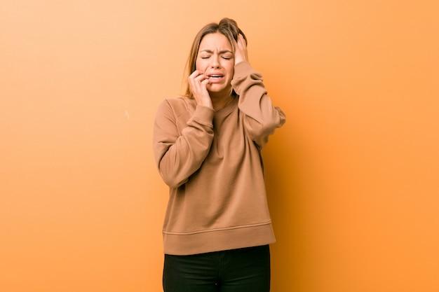 壁にぶつかり泣き叫ぶ本物の若いカリスマ的な実在の女性。 Premium写真