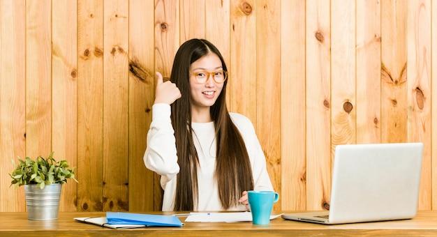 Молодая китайская женщина учится на ее столе указывает пальцем пальцем прочь, смеется и беззаботный. Premium Фотографии